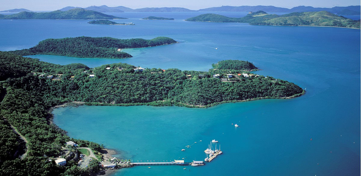 Aerial view of Shute Harbour and surrounding coast and islands with the Whitsunday Rent A Yacht jetty in the foreground