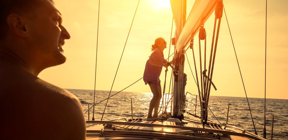 A couple learning to sail at sunset in the Whitsundays