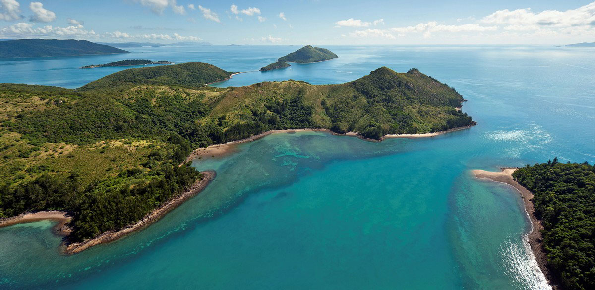 Aerial view of Whitsunday islands fringed with reefs and clear turquoise waters