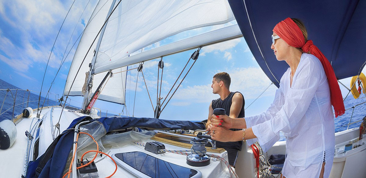 A woman turning a rope winch handle and man sail a Whitsunday Rent A Yacht charter yacht