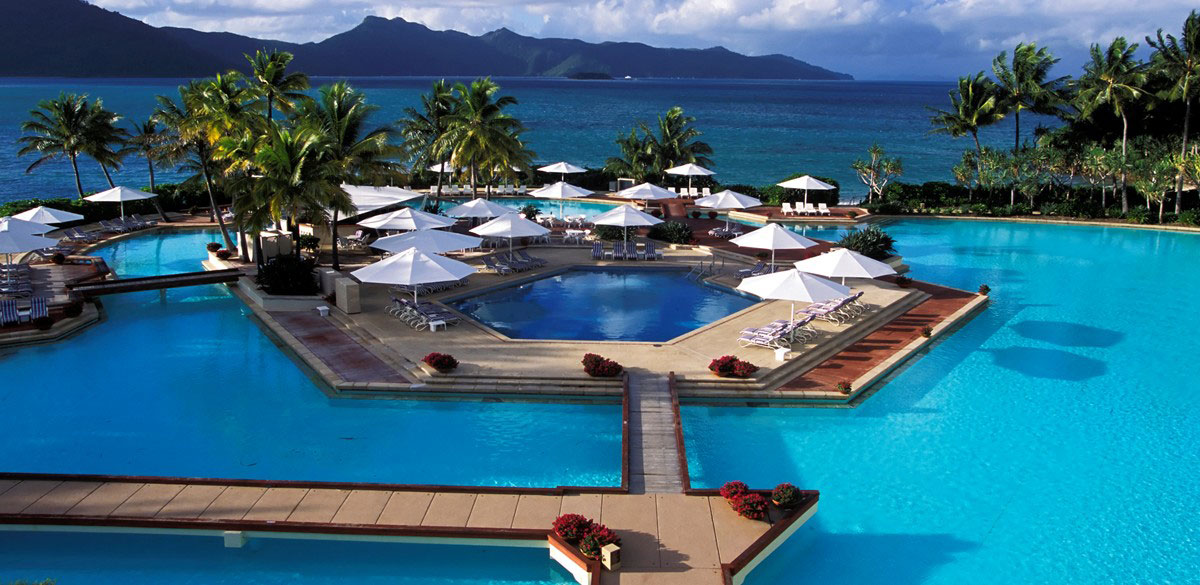 Palms surround the pools and decks at Hayman Island resort, with views of Whitsunday islands and sea beyond