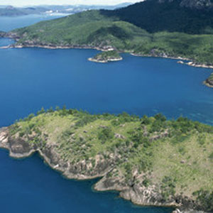 Aerial view over the two bays of Chance Bay and surrounding forested hills of Whitsunday Island